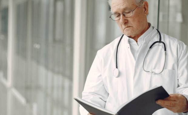 doctor reviews medical malpractice complaint in hospital hallway